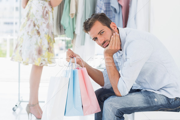 Bored man with shopping bags while woman by clothes rack Stock photo © wavebreak_media