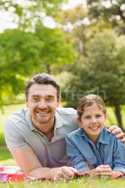Father with young daughter lying on grass in park Stock photo © wavebreak_media