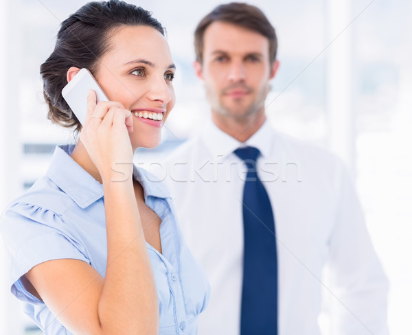 Woman on call with male colleague in background Stock photo © wavebreak_media