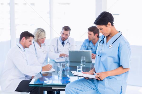 Kadın cerrah bakıyor arkadaşları toplantı Stok fotoğraf © wavebreak_media