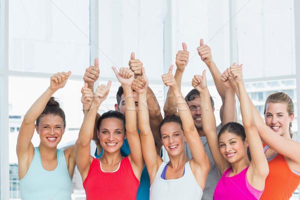 Fit people gesturing thumbs up in exercise room Stock photo © wavebreak_media