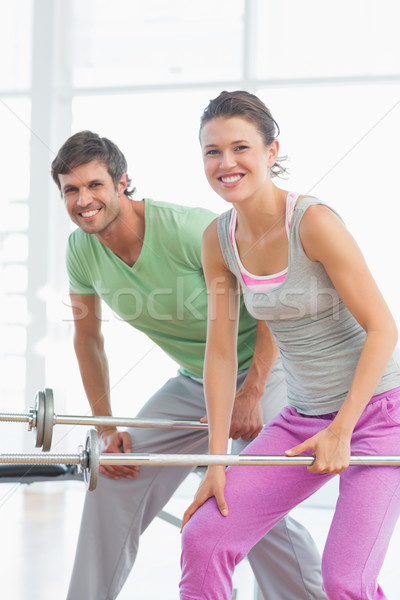 Fit young man and woman lifting barbells Stock photo © wavebreak_media