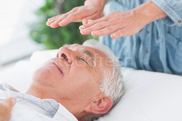 Terapeuta realizar reiki altos hombre masaje Foto stock © wavebreak_media