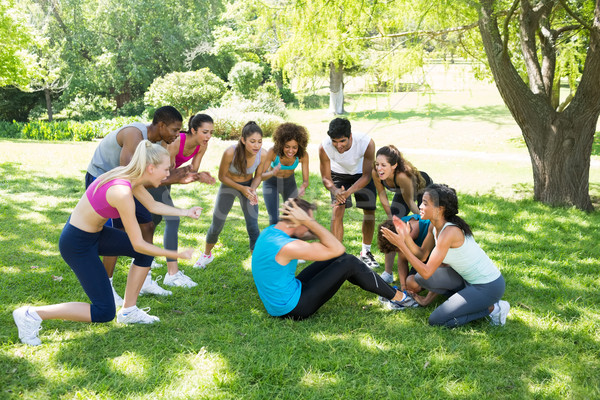 Vrienden juichen man zitten groep gras Stockfoto © wavebreak_media