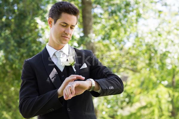 Smart groom checking time in garden Stock photo © wavebreak_media