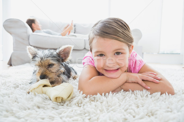 Little girl lying on rug with yorkshire terrier smiling at camer Stock photo © wavebreak_media