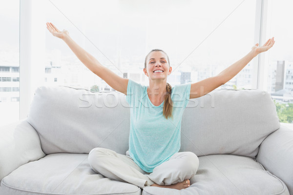Cheerful woman sitting on couch with arms outstretched Stock photo © wavebreak_media