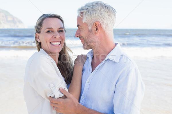 Happy couple hugging on the beach woman looking at camera Stock photo © wavebreak_media