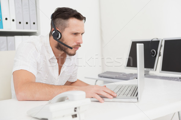Call center agent on a call at his desk Stock photo © wavebreak_media