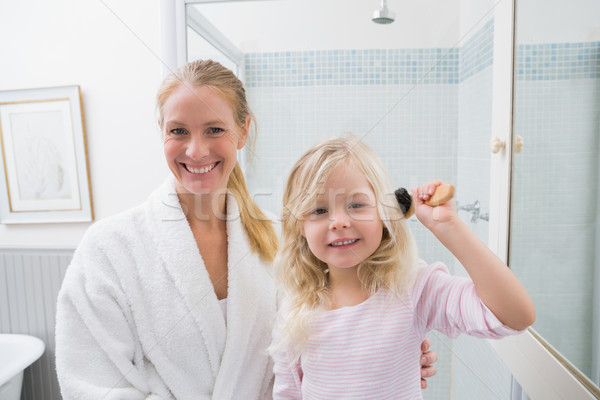 Happy mother and daughter brushing hair Stock photo © wavebreak_media