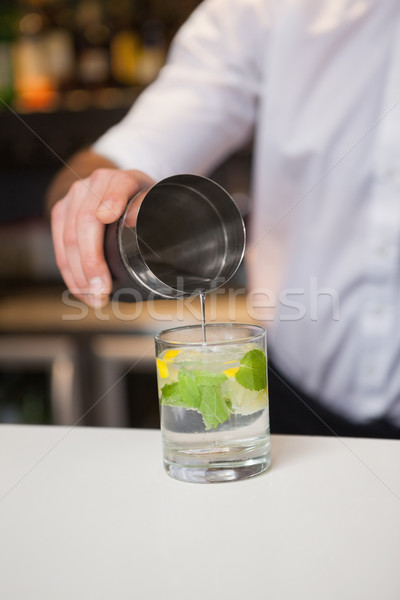Bartender pouring cocktail into glass Stock photo © wavebreak_media