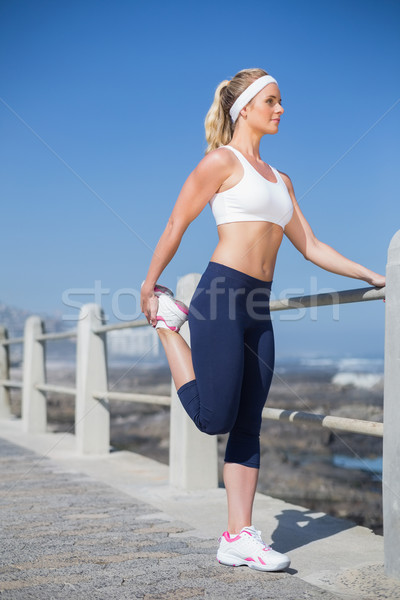 Stock photo: Fit blonde stretching on the pier