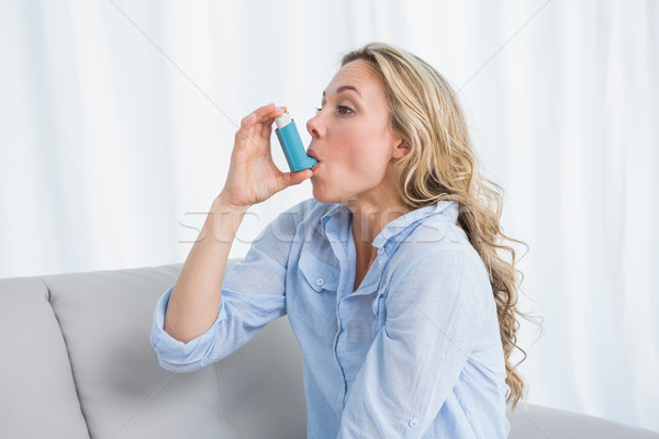 Stock photo: Blonde using her asthma inhaler on couch