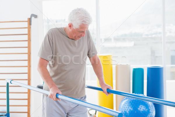 Senior man walking with parallel bars Stock photo © wavebreak_media