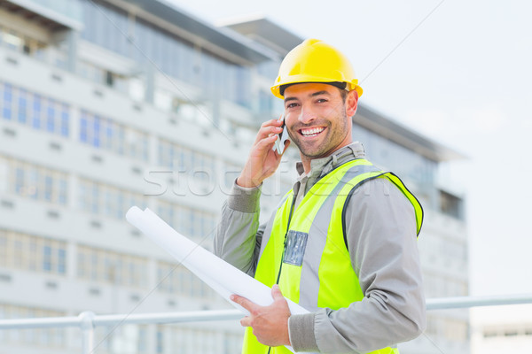 Smiling male architect with blueprints talking on mobile phone Stock photo © wavebreak_media