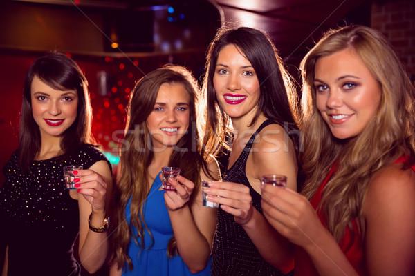 Pretty friends drinking shots together Stock photo © wavebreak_media