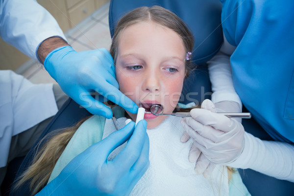 Dentist with assistant examining girls teeth Stock photo © wavebreak_media