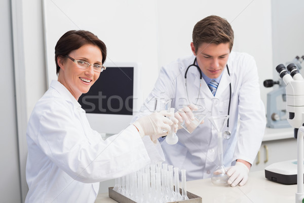 Scientists pouring chemical fluid in funnel Stock photo © wavebreak_media