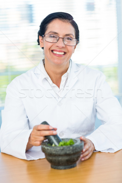 Scientist mixing herbs with pestle and mortar Stock photo © wavebreak_media