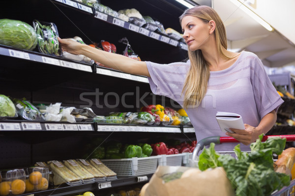 Smiling woman reading on his notepad in aisle  Stock photo © wavebreak_media