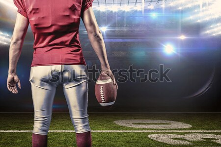 Composite image of mid section of sportsman holding american football and helmet Stock photo © wavebreak_media