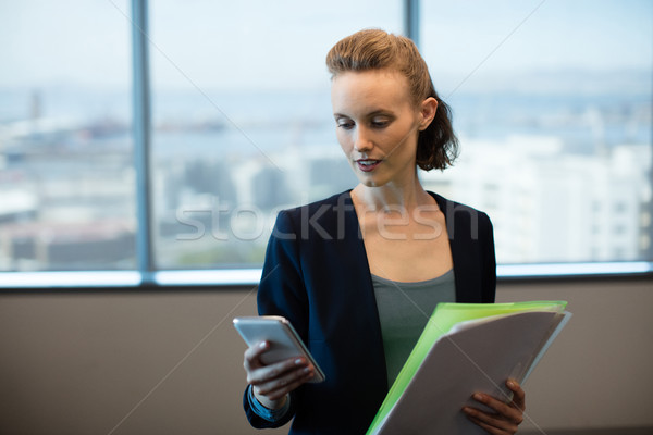 Businesswoman using mobile phone while holding files Stock photo © wavebreak_media