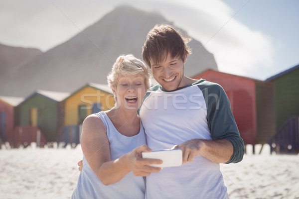 Happy mother with son using mobile phone at beach Stock photo © wavebreak_media