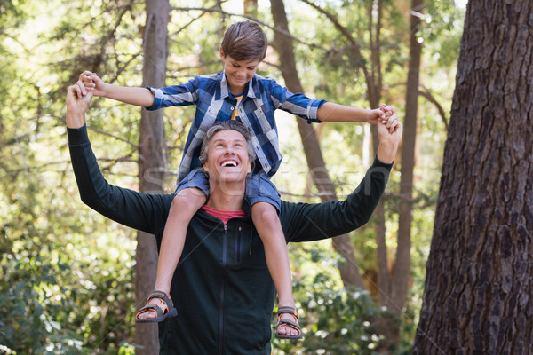 Cheerful father carrying son on shoulders in forest Stock photo © wavebreak_media