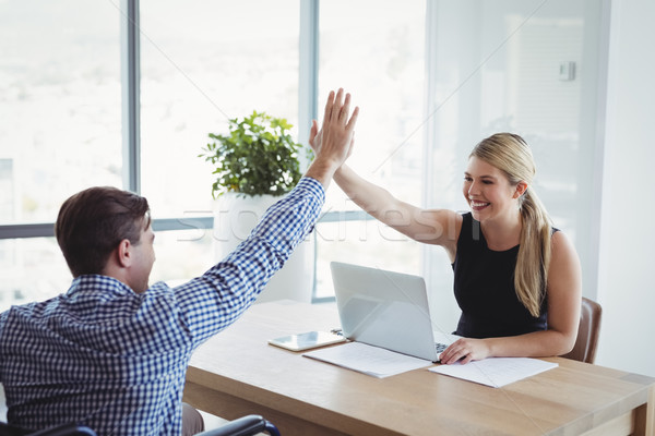 Smiling executives giving high-five to each other at desk Stock photo © wavebreak_media
