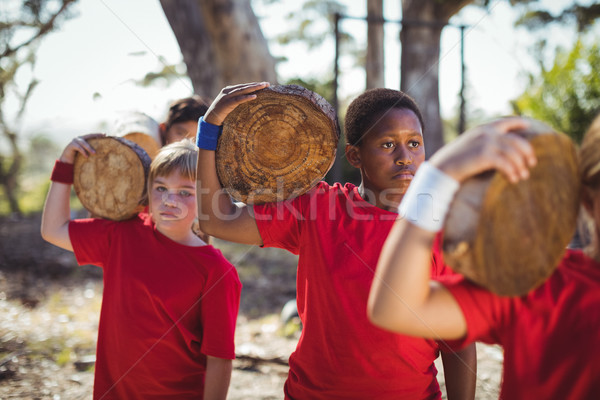 Kids carrying wooden log during obstacle course training Stock photo © wavebreak_media