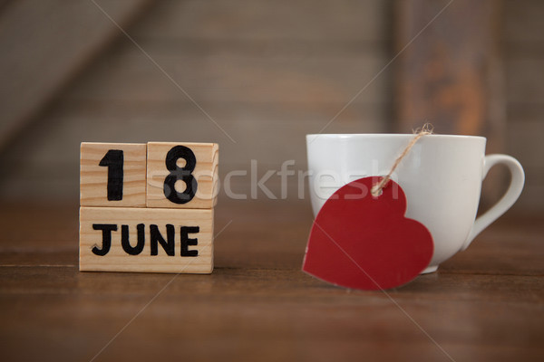Calender date by coffee cup with heart shape on table Stock photo © wavebreak_media