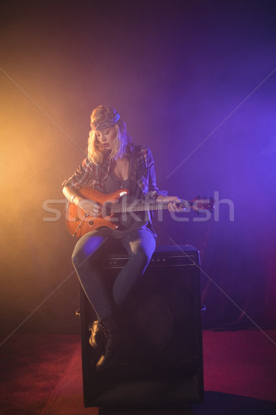 Female guitarist sitting on speaker while performing in nightclub Stock photo © wavebreak_media