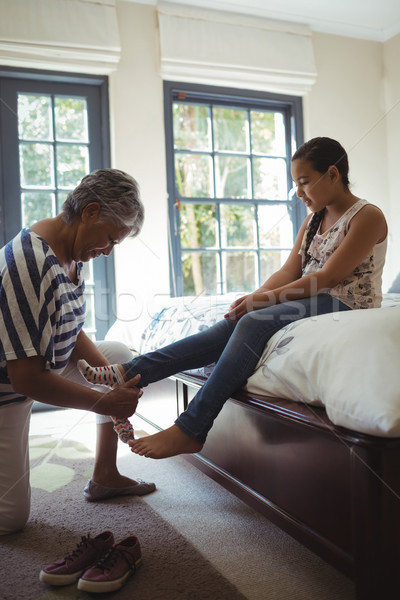 Grandmother helping granddaughter to wear socks in bed room Stock photo © wavebreak_media