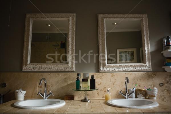 Mirrors hanging on wall by sink in bathroom Stock photo © wavebreak_media