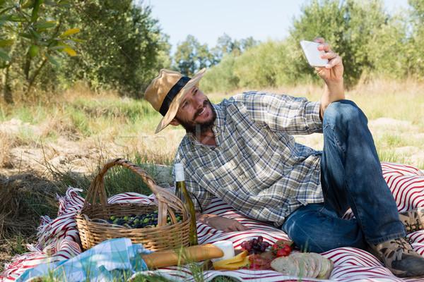 Człowiek telefonu komórkowego oliwek gospodarstwa żywności Zdjęcia stock © wavebreak_media