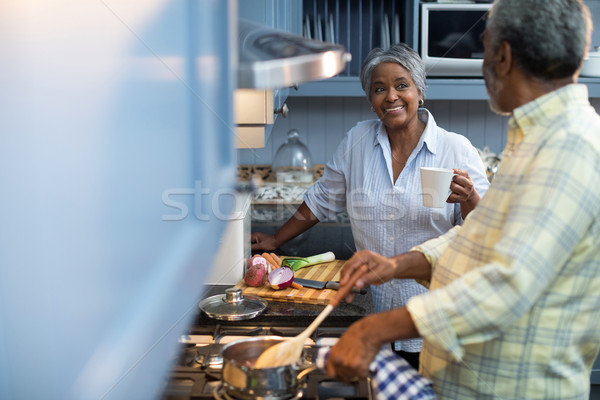 Smiling woman coffee cup talking with man preparing food Stock photo © wavebreak_media