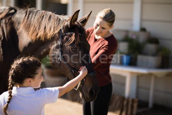 Madre hija tocar caballo sonriendo familia Foto stock © wavebreak_media
