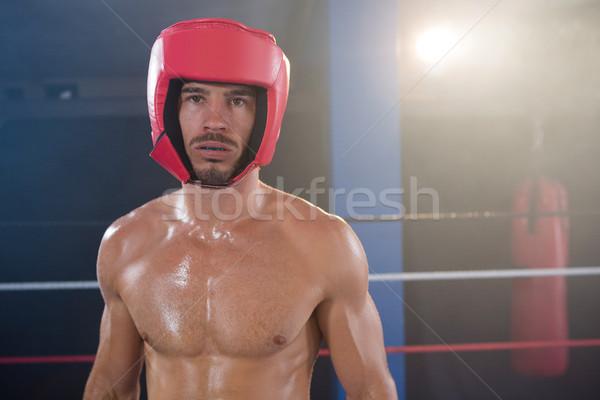 Portrait of shirtless male boxer wearing red headgear Stock photo © wavebreak_media