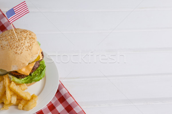 Burger decorated with american flag and french fries in plate Stock photo © wavebreak_media