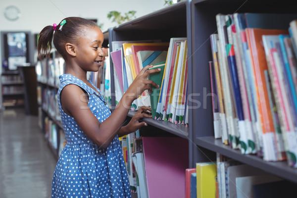 Girl choosing book in library Stock photo © wavebreak_media