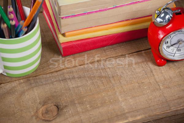 Stack of books, alarm clock and pen holder Stock photo © wavebreak_media