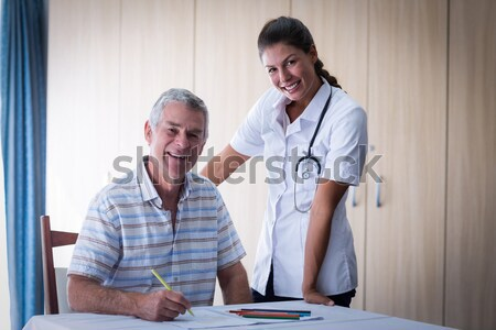 Portrait of nurse assisting senior patient in walking with walker Stock photo © wavebreak_media