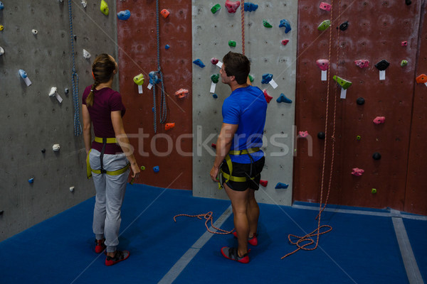 Male trainer guiding woman in climbing wall at gym Stock photo © wavebreak_media