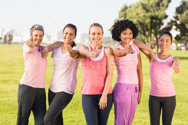Smiling women wearing pink for breast cancer and doing thumbs up Stock photo © wavebreak_media