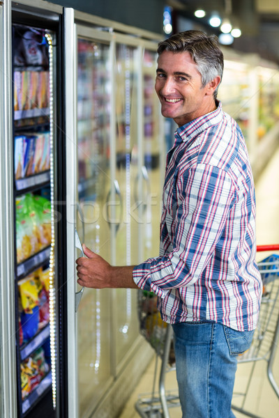 Man opening supermarkt koelkast glimlachend camera Stockfoto © wavebreak_media