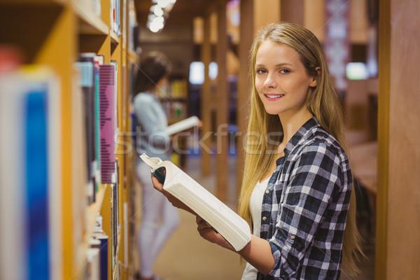 Sério estudantes leitura prateleira de livros biblioteca mulher Foto stock © wavebreak_media