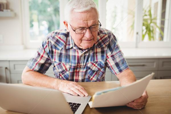 Zmartwiony starszy człowiek patrząc dokumentu za pomocą laptopa Zdjęcia stock © wavebreak_media