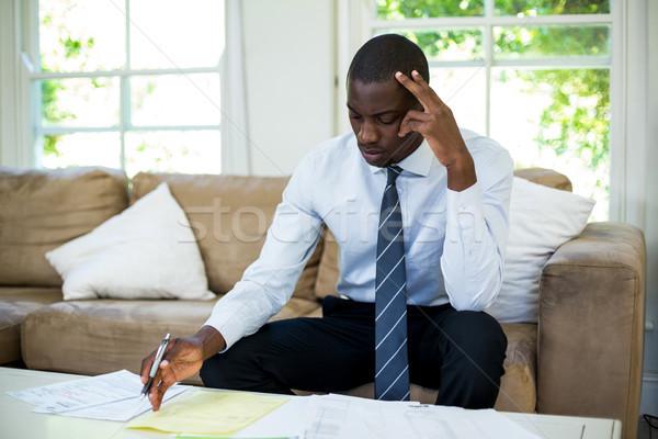 Tensed man sitting on sofa and accounting the bills Stock photo © wavebreak_media