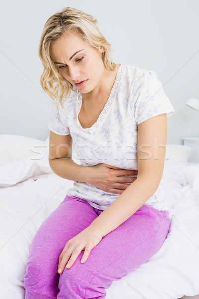 Young woman having stomach pain in bed Stock photo © wavebreak_media