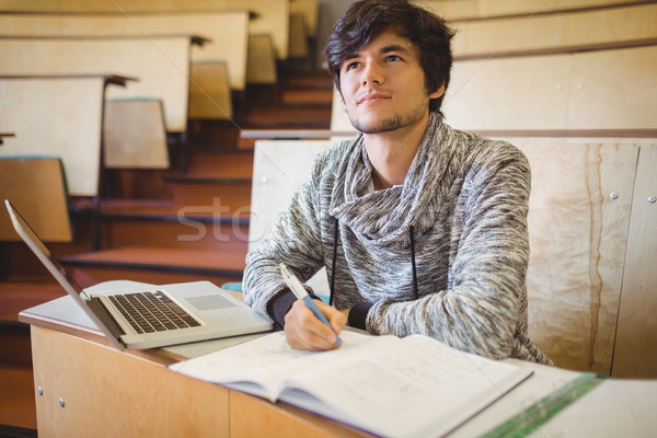 Thoughtful young student sitting at desk with book and laptop Stock photo © wavebreak_media